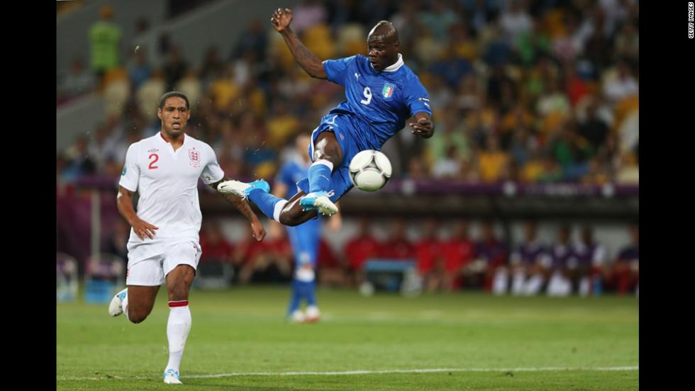 Mario Balotelli of Italy strikes the ball as Glen Johnson of England looks on.