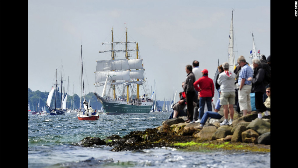 Visitors stand on the rocky shore, watching the Alexander von Humboldt II pass by.