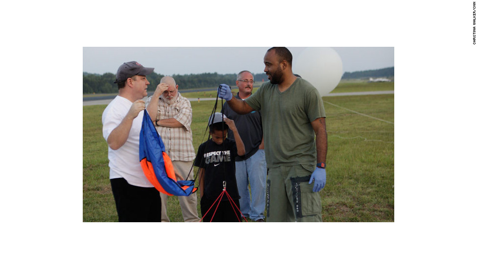 Sudduth and Rogers attach the parachute, while Rogers' 8-year-old son lends a hand.