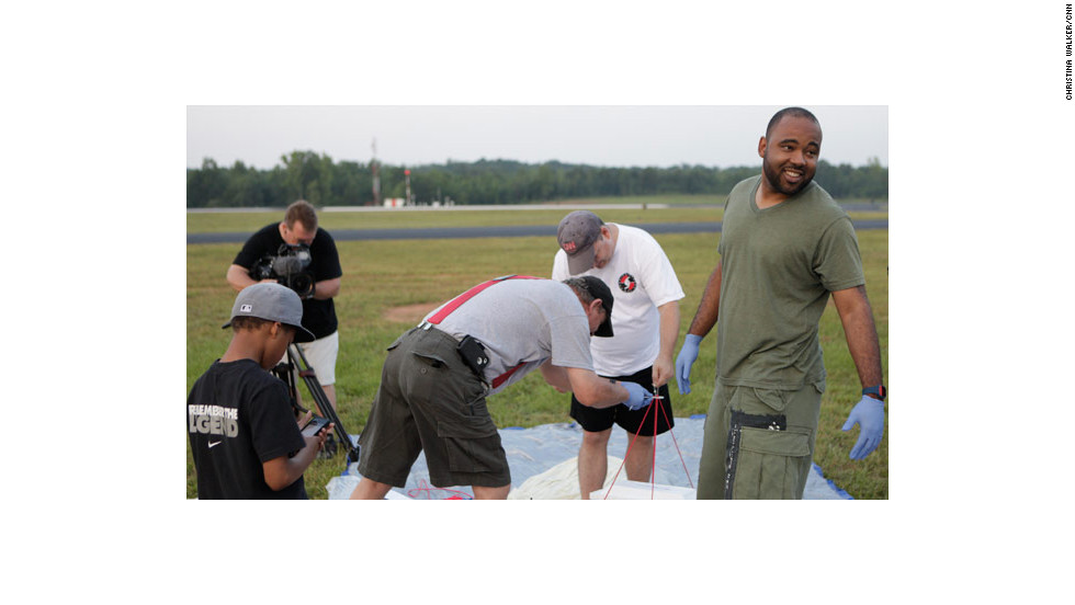 "Rogers, right, helps Erickson and hurricane tracker Mark Suddith of <a href=""http://hurricanetrack.com/"" target=""_blank"">hurricanetrack.com </a>attach the balloon's tether to the Styrofoam container."