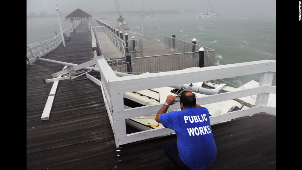 The Bradenton Beach Public Works Department's Tim Change takes photos of damage from boats hitting the pier after breaking free from their moorings.