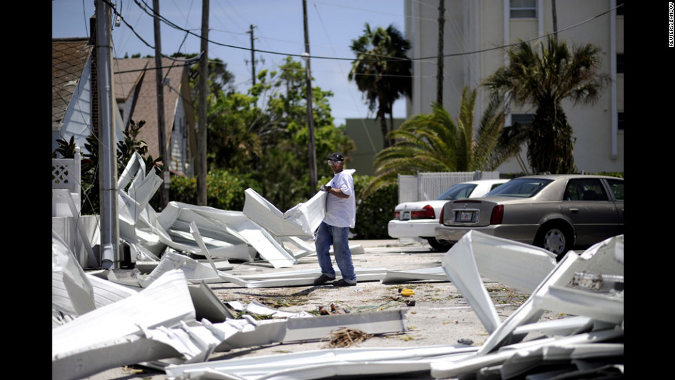 A worker begins removing debris Monday from damaged buildings in Pass-A-Grille Beach.
