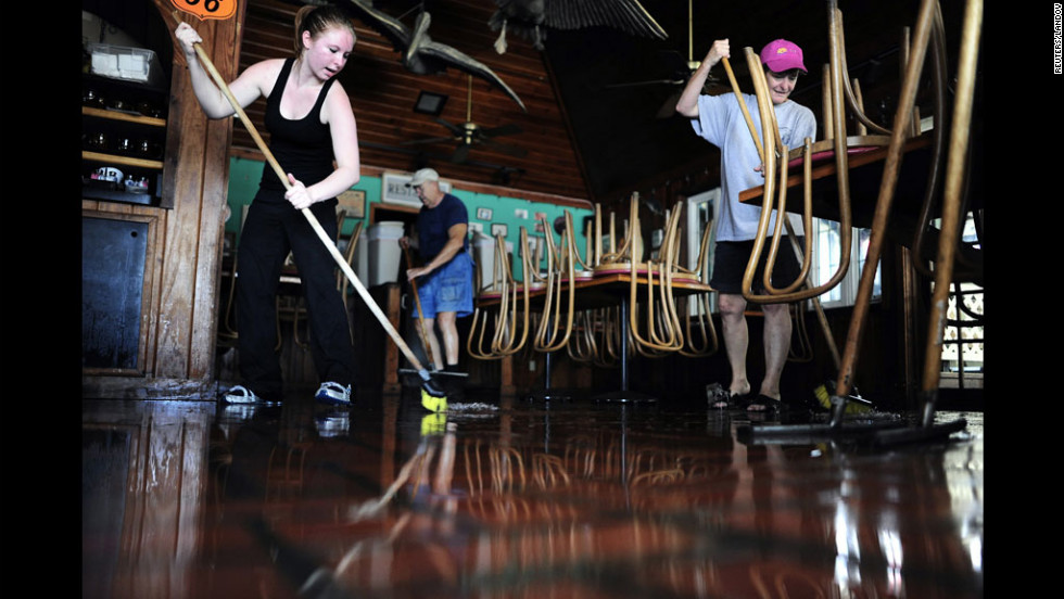 Brittany Cheak, from left, Al Church and Angie Cheak help mop up inside the Seahorse Tavern & Restaurant on Monday in St. Pete Beach, Florida.