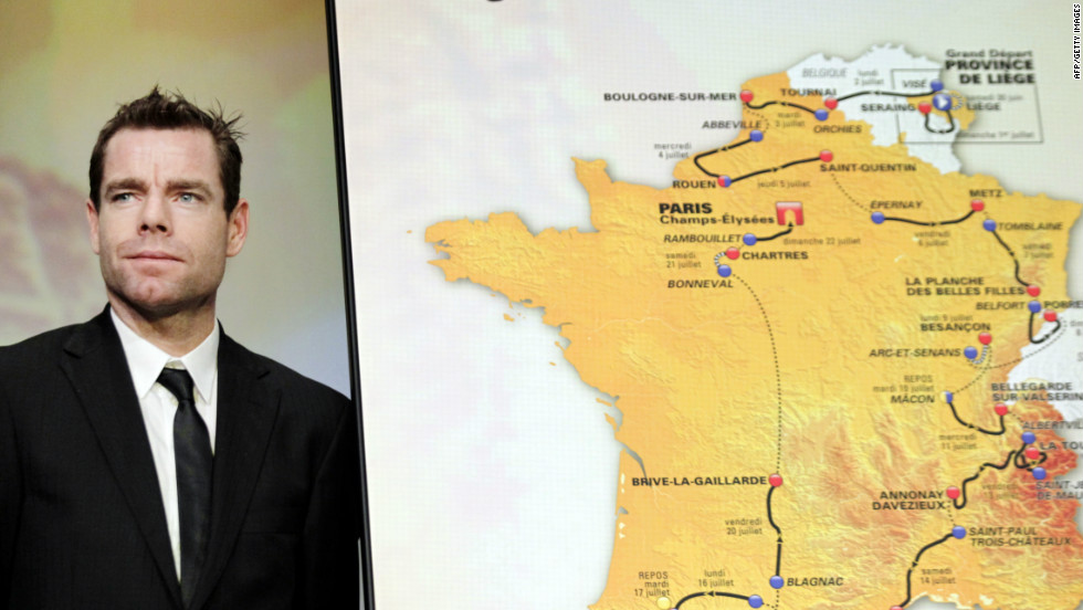 Last year's winner Cadel Evans stands next to a map showing the  3,479 km route of the 2012 Tour de France.