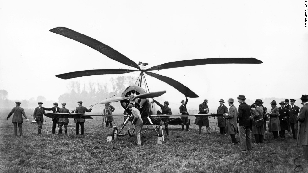 "Another air innovation gets an outing at Farnborough in 1925 as test pilot Frank Courtney talks with officials and reporters at the aerodrome before taking an ""autogiro"" for a flight."