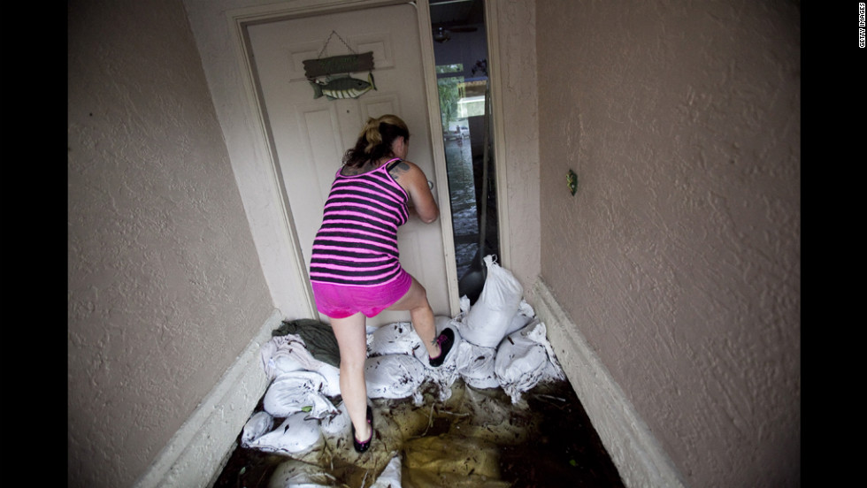 Doreen Ferrilo opens the door to her flooded home to salvage what she can before she must evacuate.