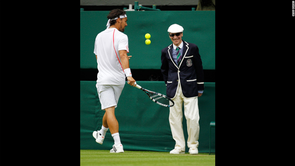Italy's Fabio Fognini entertains a line judge by bouncing two balls during his second-round match against Roger Federer of Switzerland on June 27.