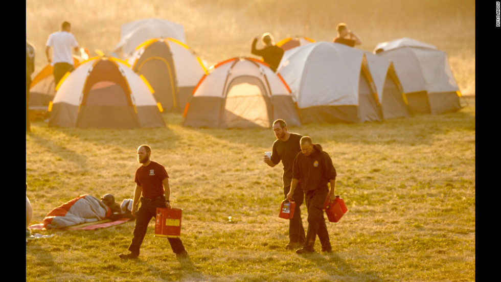 At dawn on Tuesday, firefighters stir from their tents at a camp near Holmes Middle School.