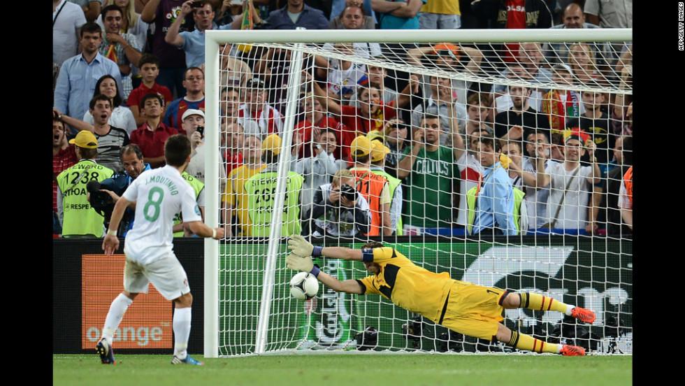 Spanish goalkeeper Iker Casillas stops a penalty kicked by Portuguese midfielder Joao Moutinho.