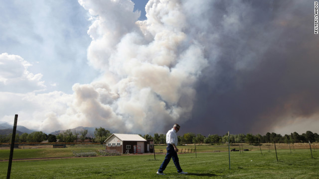 "Image #: 18415008    A man walks across a field as smoke from the Waldo Canyon fire west of Colorado Springs, Colorado fills the sky June 26, 2012.  A fast-growing wildfire in Colorado forced 11,000 people from their homes at least briefly and threatened popular summer camping grounds beneath Pikes Peak, whose vistas helped inspire the patriotic tune ""America the Beautiful"".    REUTERS/Rick Wilking (UNITED STATES - Tags: DISASTER ENVIRONMENT)       REUTERS /RICK WILKING /LANDOV"