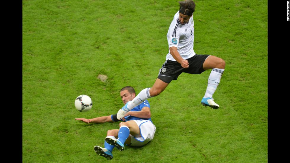 Italian defender Giorgio Chiellini slides under German midfielder Sami Khedira.