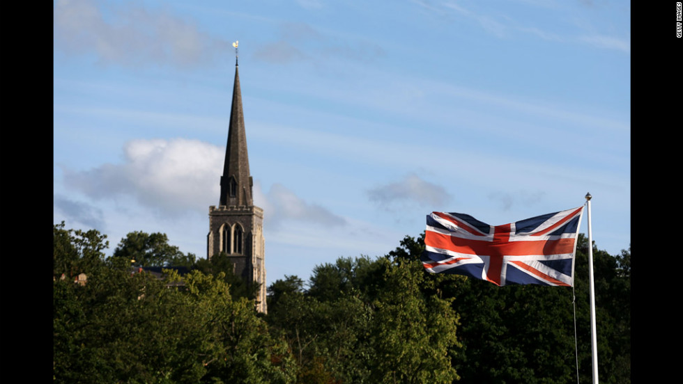 A Union Jack flaps in the breeze outside the All-England Club with the spire of St. Mary's Church in the background.