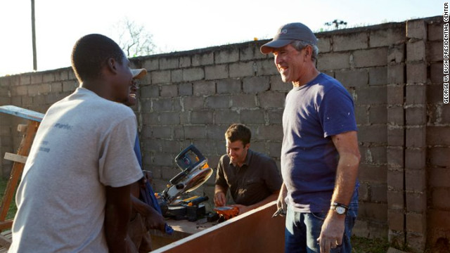 Former President George Bush helps paint and refurbish a clinic used to screen and treat cervical cancer in Kabwe, Zambia.