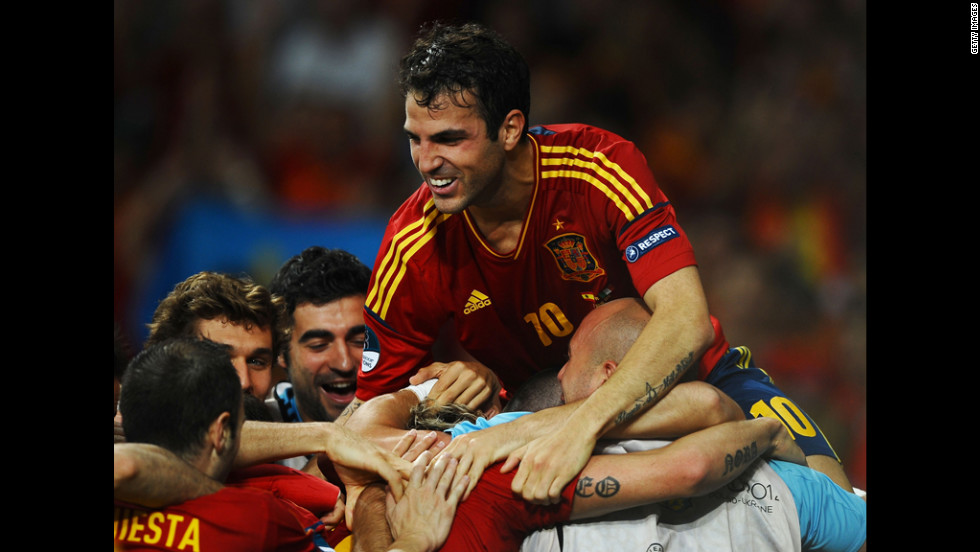 Cesc Fabregas of Spain jumps on his teammates as they celebrate after Fernando Torres scored his team's third goal against Italy.