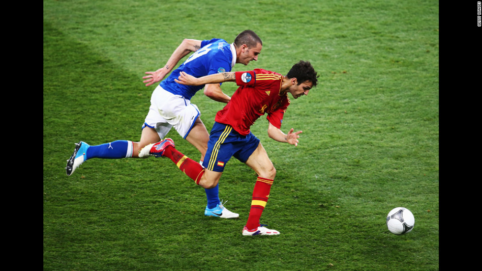 Cesc Fabregas of Spain runs with the ball past Leonardo Bonucci of Italy.