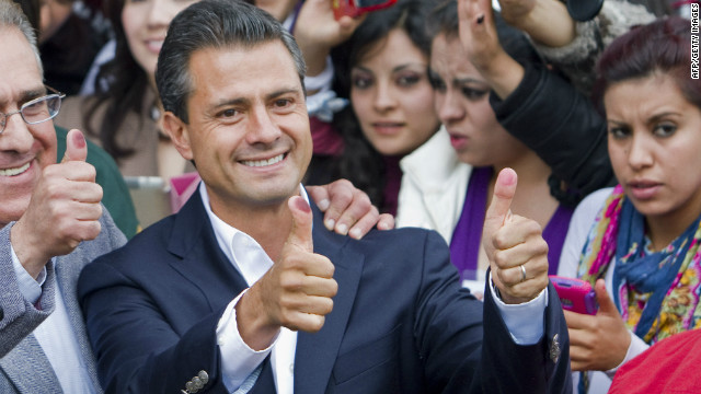 The presidential candidate for Mexico's Institutional Revolutionary Party (PRI), Enrique Pe�a Nieto, gives his thumbs up showing his ink-stained thumbs, after casting his vote in the presidential elections, in Atlacomulco, state of Mexico, on July 1, 2012.