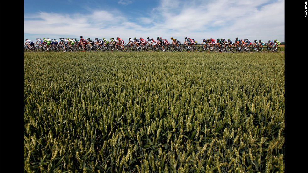 The peloton, or main group of racers, rides past a wheat field in the countryside Monday in Vise, Belgium, during stage two of the 2012 Tour de France.