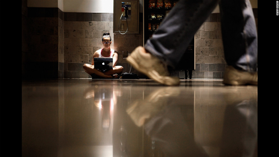 Katie Klang plugs into an electrical outlet Monday to study inside the air-conditioned Westfield Montgomery Mall in Silver Spring, Maryland. Almost half a million businesses and households in the metropolitan area were without electricity Monday.