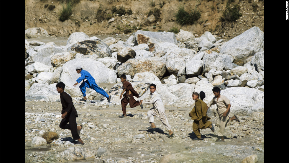 Afghan children sprint across a riverbed to recover the spent brass fired by soldiers near the village of Qandaro in the Pech River Valley of Afghanistan's Kunar province Monday.