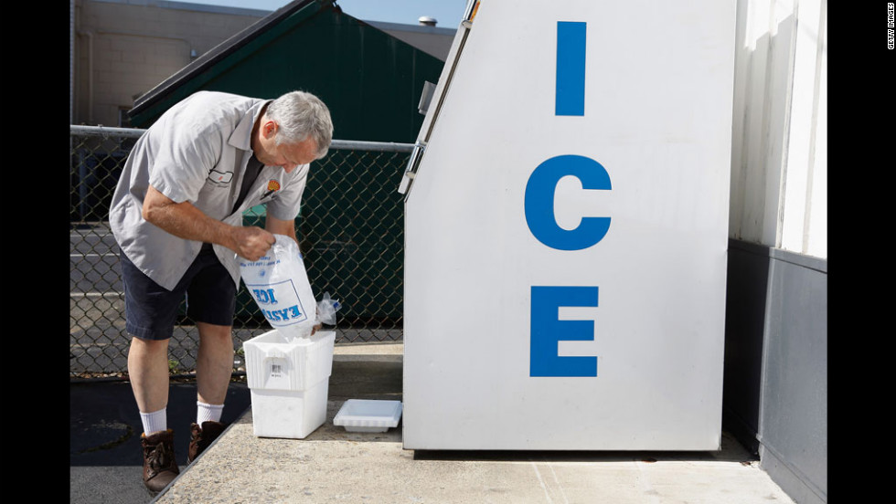 Without electricity to operate the pumps at his gas station in Silver Spring, Maryland, Ken Duckson fills a cooler with ice he cannot sell because his cash registers will not work.