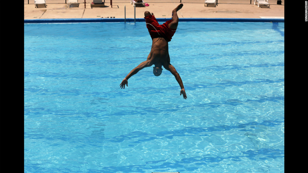 Lifeguard Niko Garcia jumps into a pool in Washington on Monday to try and beat the heat wave gripping the nation.