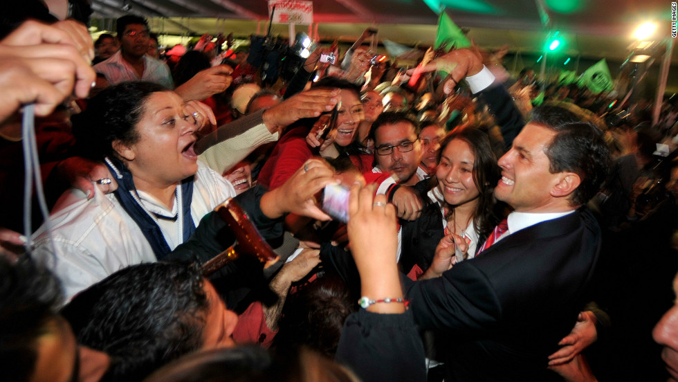 Peña Nieto greets supporters in Mexico City after polls closed and results stacked in his favor early Monday, July 2.