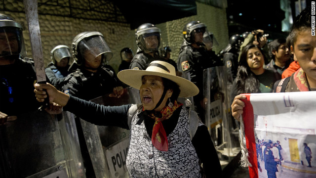 "A peasant woman who support the Mexican university student movement ""I Am #132"" blandishes a machete in front of anti-riot policemen standing guard at the entrance of the national TV network TELEVISA during a protest against the presidential candidate of the Institutional Revolutionary Party (PRI), Enrique Pena Nieto, in Mexico City on June 30, 2012 the day before presidential elections.  AFP PHOTO/ Yuri CORTEZ        (Photo credit should read YURI CORTEZ/AFP/GettyImages)"
