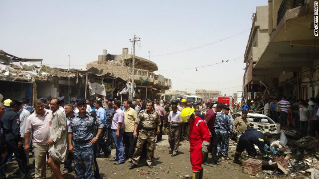 Rescue and security personnel look at the destruction following a truck bomb Tuesday in a crowded market in Diwaniya, Iraq.