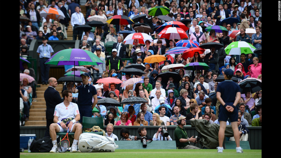 Britain's Andy Murray waits on his chair as spectators seek shelter from the rain during his men's singles quarter-final match against Spain's David Ferrer on Wednesday.