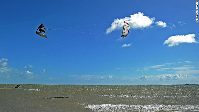 A man jumps as he kite surfs into the sea