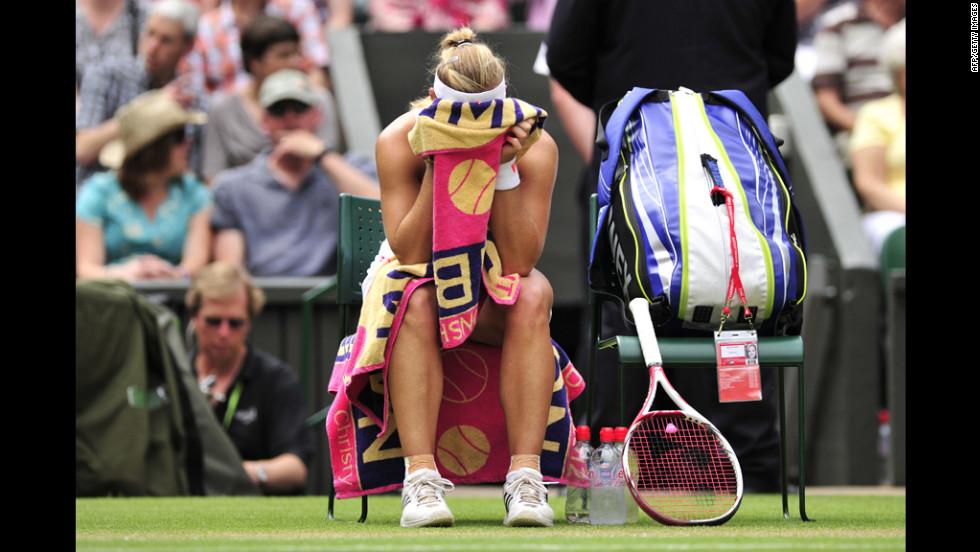 Kerber buries her head in her towel during a break between games in her Ladies' Singles semifinal defeat to Radwanska.