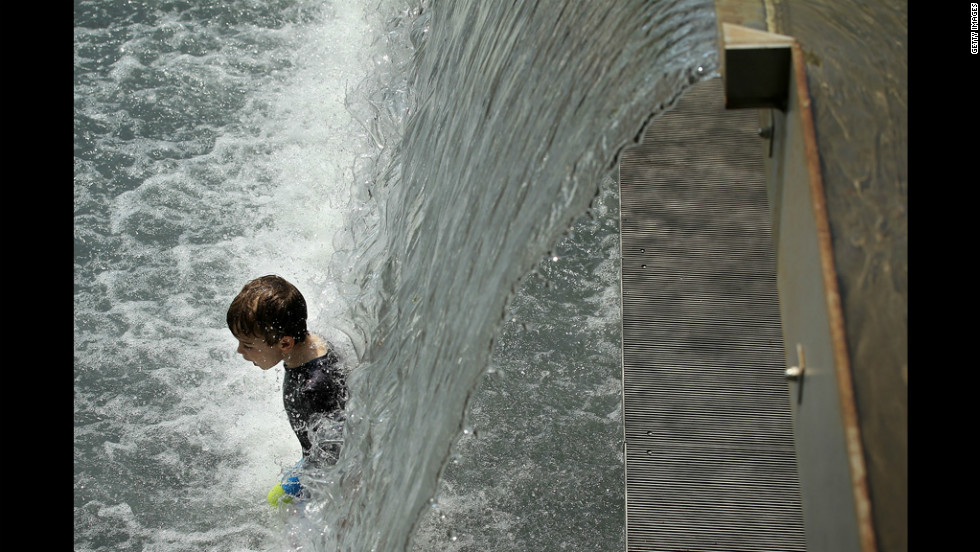 A boy enjoys the waterfall in the Yards Park fountain on Thursday.