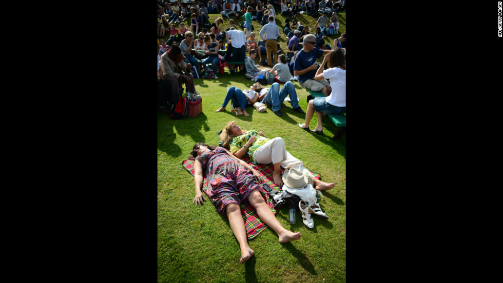 Spectators relax in the afternoon sun on Henman Hill (aka Murray Mound) on Thursday.