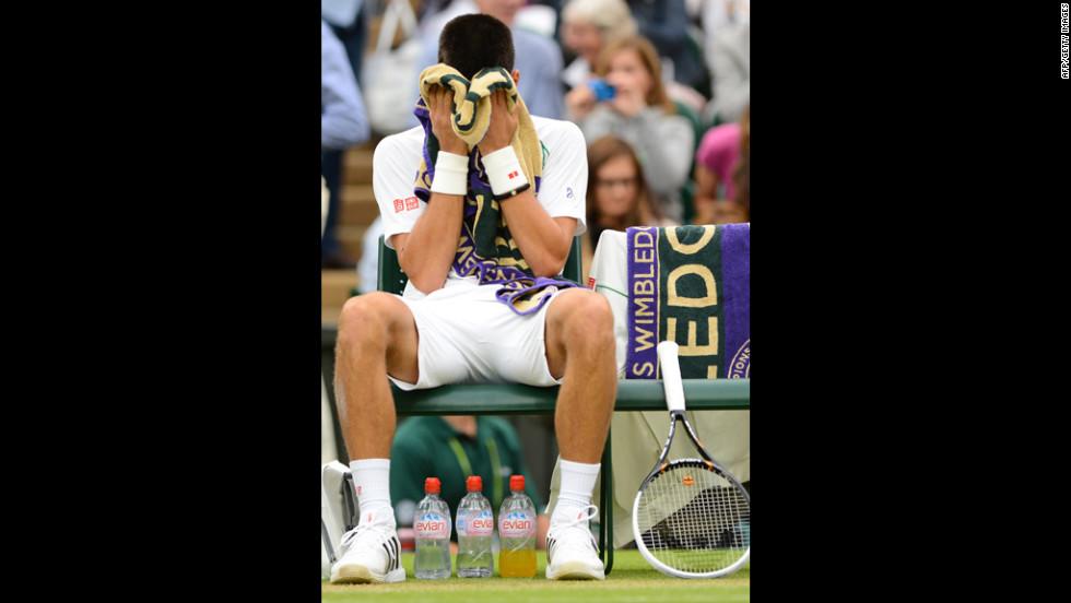 Novak Djokovic buries his head in his towel during a break between games against Roger Federer on Friday.