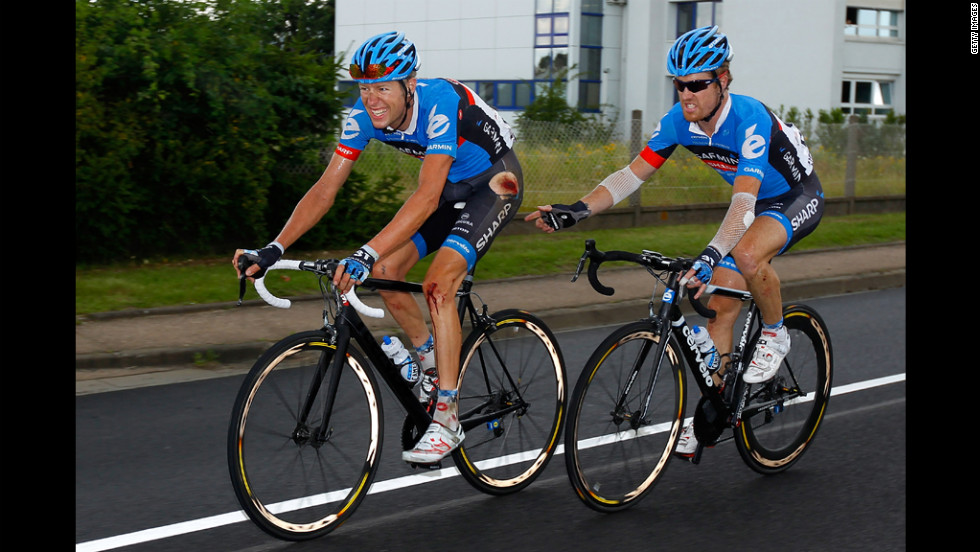 A bloodied Ryder Hesjedal of Canada, riding for Garmin-Sharp, is accompanied by teammate Tyler Farrar of the United States as they ride to the finish of Stage 6 in Metz.  Hesjedal was involved in a crash 25 kilometers from the end of the stage and was separated from the yellow jersey group.