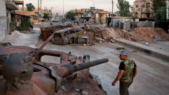 A member of the Free Syria Army walks past a destroyed Syrian forces tank in the town Atareb in northern Aleppo province.
