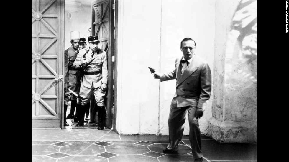 Ugarte holds the letters of transit that many refugees waiting in Casablanca would like to get their hands on. Here he brandishes a gun as he attempts to flee from French authorities.