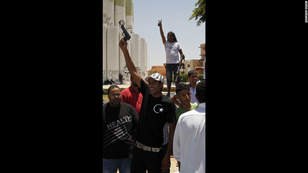 Libyan protesters wave pistols and peace signs.