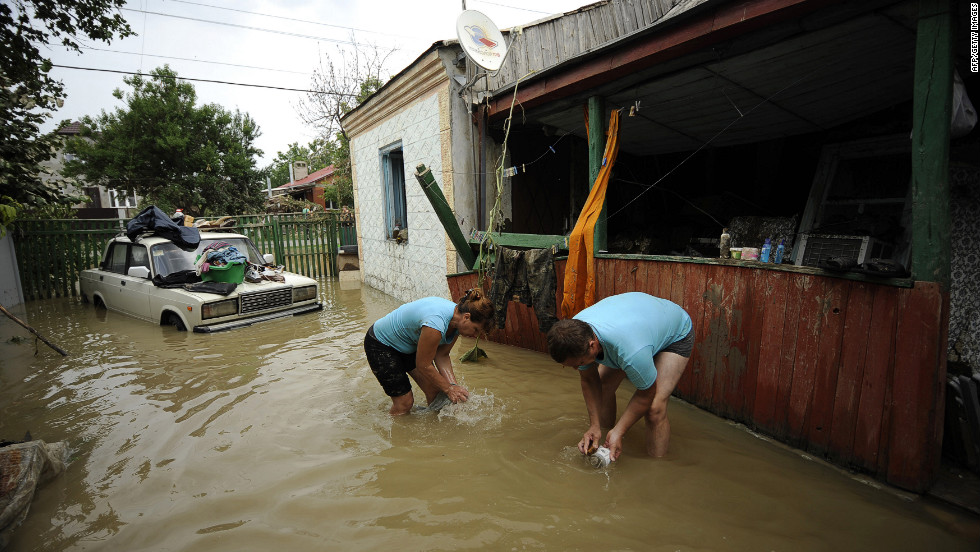 Locals work outside a home in Krymsk where floodwaters still stand Sunday.