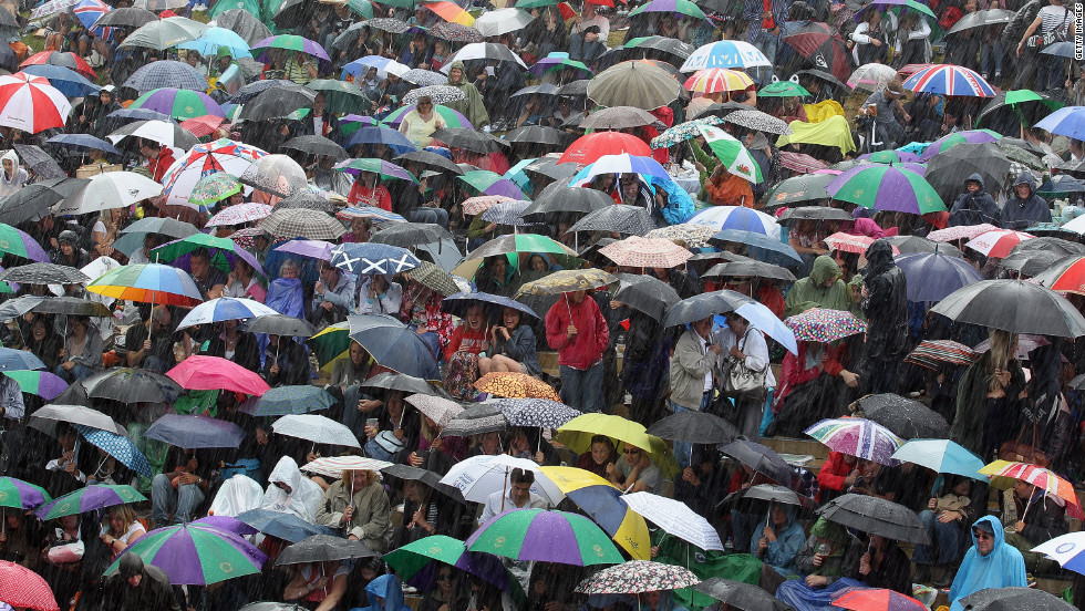 Tennis fans shelter from a heavy downpour that developed during the match Sunday.