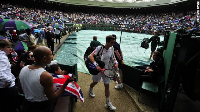Britain's Andy Murray leaves court during a rain delay in his men's singles final match against Switzerland's Roger Federer on day 13 of the 2012 Wimbledon Championships tennis tournament at the All England Tennis Club in Wimbledon, southwest London, on July 8, 2012. AFP PHOTO / GLYN KIRK     RESTRICTED TO EDITORIAL USE        (Photo credit should read GLYN KIRK/AFP/GettyImages)