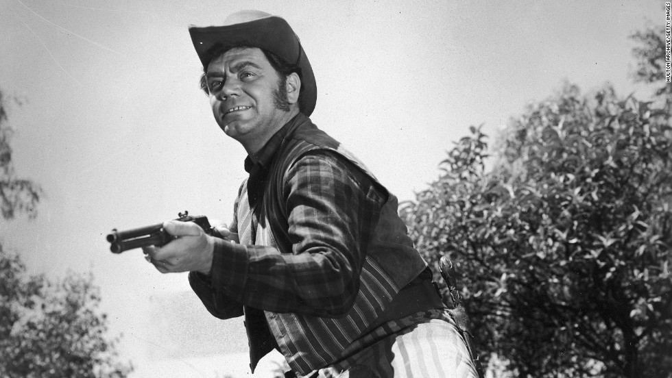 Ernest Borgnine steadies his rifle while acting in a Western film circa 1955.