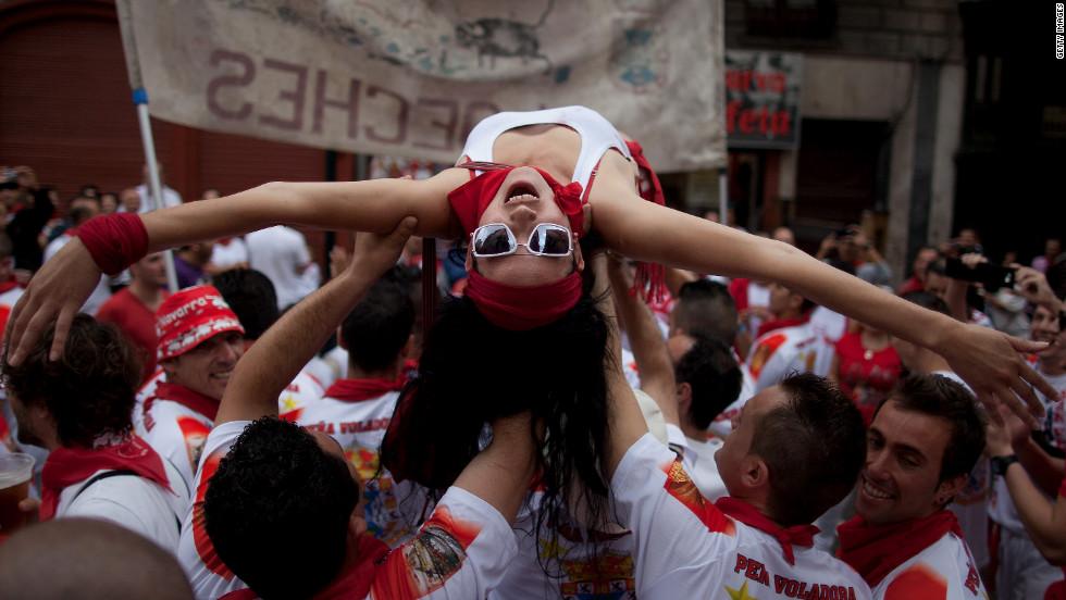 Revelers celebrate during the Pena Voladora parade on Estafeta Street on Saturday, July 7.