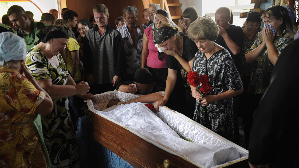 Friends and relatives surround the body of Ostapenko, who was killed during flooding in the village of Moldavskoe.