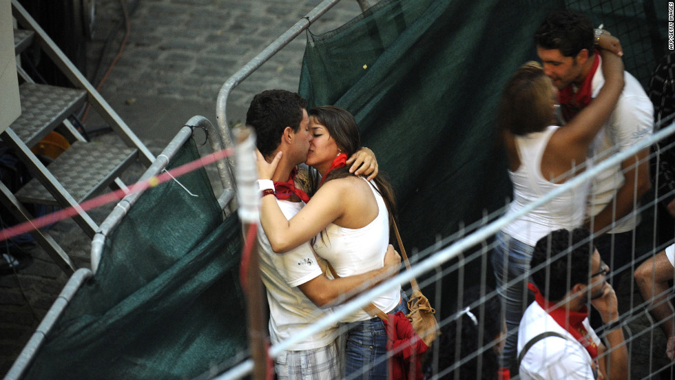 Two couples kiss as they wait for the fourth bull run to begin Tuesday.