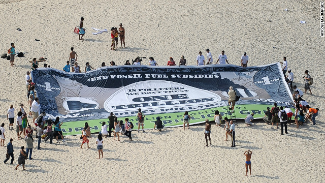 Activist unveil a banner on Copacabana beach to ask world leaders to end fossil fuel subsidies