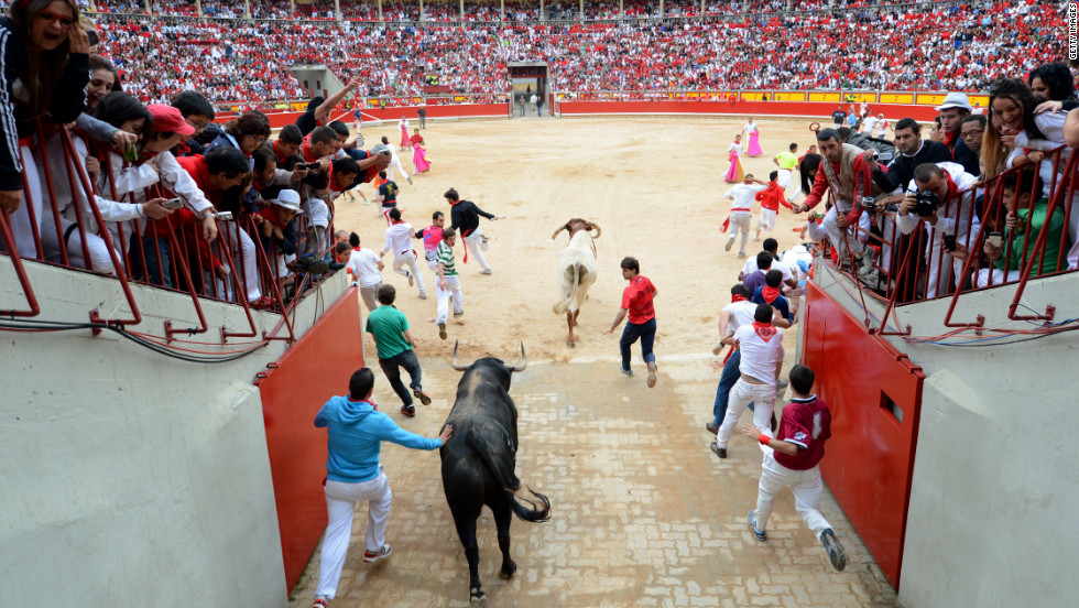 Participants run through the entrance of the bullring Wednesday on the fifth day of the festivities.