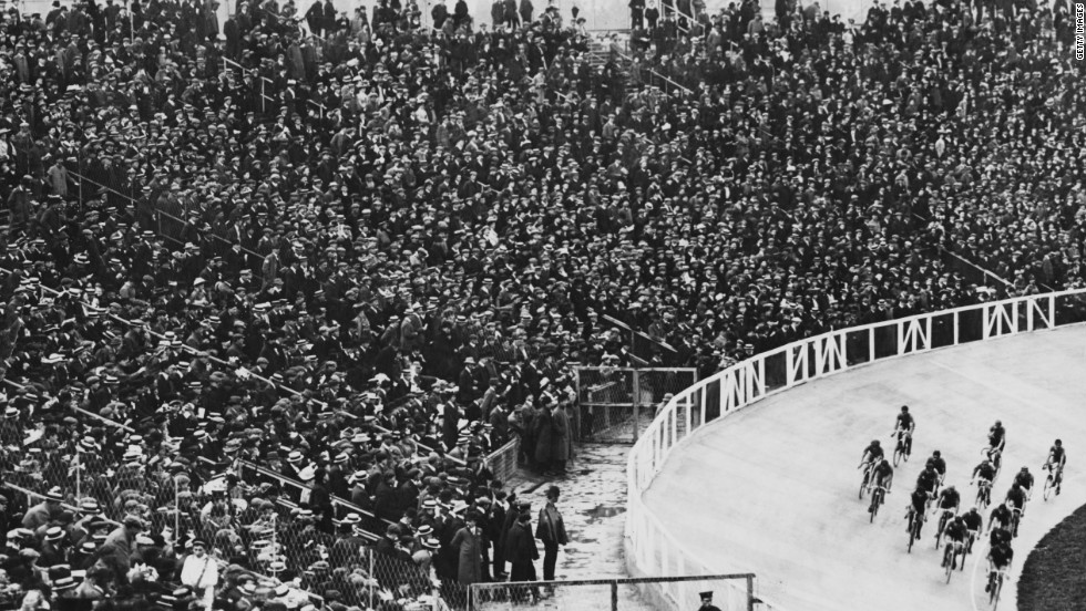 A packed stadium cheers on cyclists during a race. More than 100 years later, the 2012 London Olympics boasts a specially-built Velodrome for cycling, with seating for 6,000 competitors.