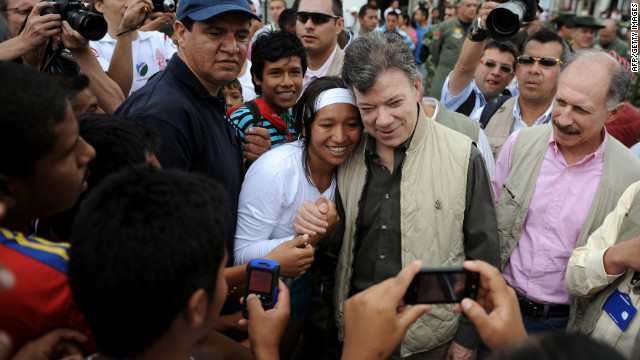 Colombian President Juan Manuel Santos (2nd-R) has his picture taken with a resident of the municipality of Toribio, department of Cauca, Colombia, upon his arrival on July 11, 2012. The local indigenous natives are asking the Colombian army and the FARC to pull back from their territories out of fear of being caught in the combats.