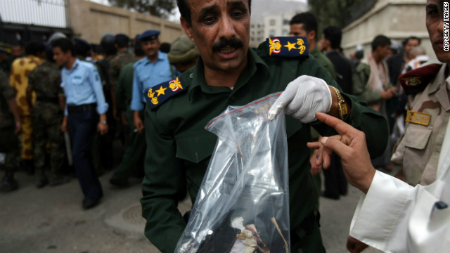 A Yemeni police officer holds evidence at the site of an explosion at a police academy in Sanaa on July 11, 2012.